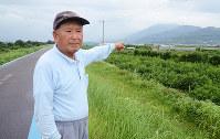 紀の川沿いの桃畑を見渡す前尾和男さん。指さす先には戦時中、飛行場が整備されていた=和歌山県紀の川市で、石川裕士撮影