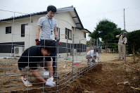 Local government workers install a wire fence around a house to keep out wild boars, in Namie, Fukushima Prefecture, on July 27, 2017. (Mainichi)