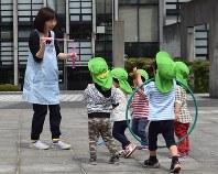 散歩先の広場でシャボン玉を使って遊ぶグローバルキッズ春日園の保育士と園児たち=東京都文京区で4月17日、鳴海崇撮影