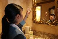 グラスに汚れがないかチェックする飯塚さん=千葉県浦安市の「東京ディズニーシー・ホテルミラコスタ」で、篠崎真理子撮影