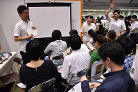 Students listen to an explanation at a company booth at an internship event held at Tokyo Big Site in the capital's Koto Ward, on July 8, 2017. (Mainichi)