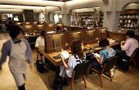 「おひとりさま」用の大テーブル席は図書館のよう=東京都豊島区の「梟書茶房」で、小川昌宏撮影