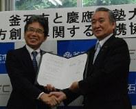 協定書に署名後、握手を交わす河添健・慶応大総合政策学部長(左)と野田武則・釜石市長=釜石市役所で