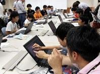 立方体を自動的に描くプログラムを組みながら、入力する角度を分度器で確かめる児童=松江市で