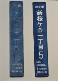 設置から20年以上たち、字が消えかかった街区表示板(左)と補修後の表示板