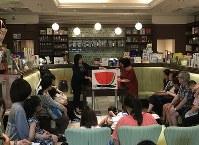 絵本「ありとすいか」を読む絵本専門士たち=東京都千代田区神田神保町2のブックハウスカフェで5日