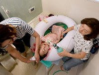 Eri Ohizumi, right, uses a breathing device to send air into the lungs of her daughter Saho, center, who has spinal muscular atrophy, while she is given a bath in a special inflatable plastic tub matching her height in Tokyo on May 30, 2017. Ohizumi continues to work on a trial-and-error basis to find bathing solutions for children with severe disabilities. (Mainichi)