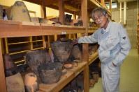 復元した縄文土器について説明する学芸員の赤石慎三さん=苫小牧市埋蔵文化財調査センターで