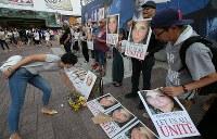 ヘザー・ヘイヤーさんを追悼し、無言で反差別の意思を表示する人たち。献花する人の姿もあった=東京・渋谷のハチ公前広場で2017年8月27日午後4時34分、後藤由耶撮影