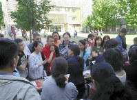 北京の公立中学校の学校開放日で、入学制度や教育方針、設備を熱心に質問する保護者たち=2017年5月6日午前8時35分、河津啓介撮影