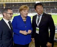 メルケル独首相(中央)らと「ドイツ体操祭」を観戦する渡辺会長(右)=FIG提供