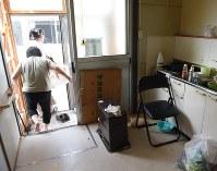 仮設開成住宅団地の部屋から引っ越しの荷物を運び出す女性と次男。壁や床に6年の歳月が染み込んでいた=石巻市で