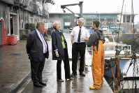 EUとの離脱交渉が始まるのを前に漁場を訪れて漁業関係者らと話すメイ英首相(左から2人目)=英南部プリマスで2017年、ロイター