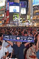 People celebrate in Tokyo's Shibuya Ward on the evening of Aug. 31, 2017, after Japan defeated Australia to win a berth in the 2018 soccer World Cup finals in Russia. (Mainichi)