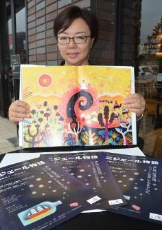 動く絵本のポスターを前に、絵本「ニジェール物語」を手にする原作者の福田英子さん=守谷市で