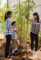 Princess Mako, right, harvests vegetables with Princess Kako and Prince Hisahito on the grounds of their residence in Minato Ward, Tokyo, in August 2014 when she was 22. (Photo courtesy of the Imperial Household Agency)