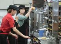 「主婦向けクルー体験会」でチーズバーガーを作る参加者(右)=東京都中野区のマクドナルド中野セントラルパーク店で2017年9月5日、今村茜撮影
