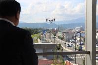 協定締結式の後、デモ飛行するドローン(中央)。左は谷藤裕明盛岡市長=盛岡市の盛岡中央消防署で