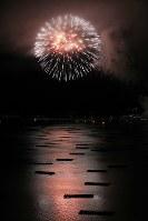 カキ養殖のいかだが並ぶ穏やかな山田湾に打ち上げられる花火=岩手県山田町で2017年8月14日、小出洋平撮影