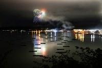 街あかりに囲まれた穏やかな山田湾に花火が打ち上がると、カキ養殖用のいかだが浮かび上がる=岩手県山田町で2017年8月14日、小出洋平撮影
