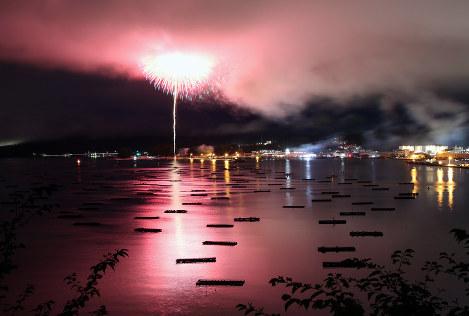港町の明かりを取り戻した山田湾に打ち上げられた花火が、洋上に並ぶカキ養殖のいかだを照らし出した=岩手県山田町で2017年8月14日、小出洋平撮影
