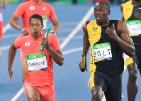 Naotsune Umemura's award-winning photo of Usain Bolt, right, and Aska Cambridge during the 100-meter relay race at the 2016 Rio Olympics. (Mainichi)