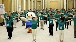 「みんなでラジオ体操プロジェクト」のイベントでラジオ体操をする小池百合子・東京都知事(中央)ら=2017年7月24日、長谷川直亮撮影