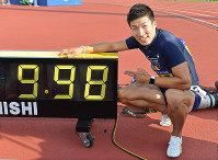 Yoshihide Kiryu poses in front of a clock showing that he finished the men's 100-meter sprint in 9.98 seconds at an intercollegiate meet at the Fukui Prefectural Athletic Park in Fukui on Sept. 9, 2017. (Mainichi)