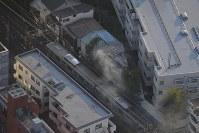 火災があったボクシングジム(中央上)。中央は停車した小田急線の車両=東京都渋谷区で2017年9月10日午後5時2分、本社ヘリから西本勝撮影