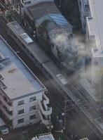 火災があったボクシングジム(中央上)。中央は停車した小田急線の車両=東京都渋谷区で2017年9月10日午後4時56分、本社ヘリから西本勝撮影