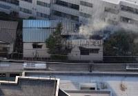 火災があったボクシングジム(中央)。下は停車した小田急線の車両=東京都渋谷区で2017年9月10日午後4時56分、本社ヘリから西本勝撮影