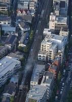 沿線のボクシングジム(左下)の火災が延焼し、停車した小田急線の車両(中央)=東京都渋谷区で2017年9月10日午後4時58分、本社ヘリから西本勝撮影