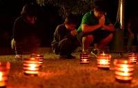 紀伊半島豪雨から6年を迎えた被災現場で、ともされたキャンドルに手を合わせる人たち=和歌山県那智勝浦町で2017年9月4日午前1時32分、平川義之撮影