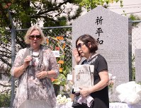 言葉を詰まらせながら記念碑前で父の体験などを語るモターショーさん(左)