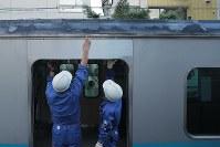 建物火災の影響で屋根が焦げた小田急小田原線の列車を調べる作業員=東京都渋谷区で2017年9月10日午後5時41分、和田大典撮影