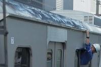建物火災の影響で屋根が焦げた小田急小田原線の列車を調べる作業員=東京都渋谷区で2017年9月10日午後5時38分、和田大典撮影
