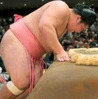 貴景勝との一番で足を負傷し、土俵にもたれかかる宇良=東京・両国国技館で2017年9月11日、和田大典撮影