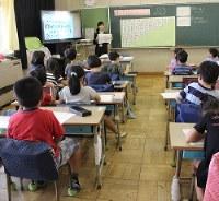 小学校の授業で大型テレビを使い、計算の練習をさせる教育実習生。教員需要の減少に伴って教育学部の改革が進む=東京都小平市で