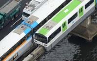 レール上で停止したモノレール(右)。左は乗客を救助したモノレール=東京都大田区で12日午後3時31分、本社ヘリから藤井達也撮影