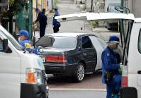 射殺現場に残された車の周辺を調べる捜査員ら=神戸市長田区で2017年9月12日午後1時21分