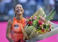 現役最後の試合を終え、引退セレモニーで花束を手に笑顔を見せる伊達公子=有明テニスの森で2017年9月12日、手塚耕一郎撮影