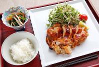 焼き色が付いて照りがある鶏モモ肉のすだち焼き(右)とホウレンソウのおひたし(左奥)=菅知美撮影