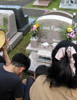 愛猫と家族の眠る墓に親子3代で手を合わせる一家。墓石には猫のイラストも=町田いずみ浄苑で