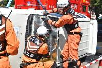 車内の人を救助しようとフロントガラスを外そうとする参加者=岐阜県中津川市の中央道中津川チェーン脱着場で