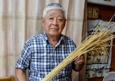 稲穂を手にアラセツ行事について語る窪田さん