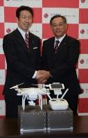 協定を結んだ米山知事(左)と損保ジャパン日本興亜の高岸執行役員。手前はドローン=新潟市中央区の県庁で