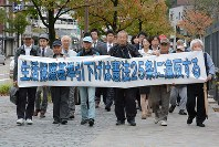 Plaintiffs and lawyers head to the Kanazawa District Court to file a lawsuit against the lowering of public assistance funds in Kanazawa, Ishikawa Prefecture, on Oct. 15, 2014. (Mainichi)