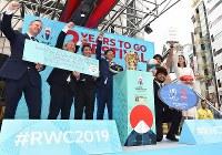 ラグビーW杯日本大会開幕まで2年となり、一般公開された優勝トロフィー「ウェブ・エリス・カップ」を前にラグビー日本代表の堀江翔太選手(右手前)らと記念撮影に応じるスポーツ庁の鈴木大地長官(左から4人目)ら=東京都渋谷区で2017年9月20日午前11時35分、宮間俊樹撮影
