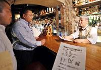 飲食店の経営者(右)にチラシを手渡し、不当な要求を受けていないか聞き取り調査をする大阪府警の捜査員=大阪市中央区で2017年9月19日