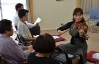 大熊町民のそばで演奏を披露する仙台フィルハーモニー管弦楽団のメンバー=会津若松市一箕町の松長近隣公園仮設住宅で